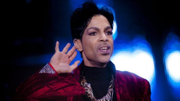 Aufnahme von Prince an einem Konzert, er hält eine Hand ans Ohr, zu signalisieren, dass er die Fans singen hören möchte.