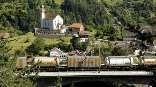 Ein Güterzug mit Lastwagencontainern auf der Gotthardachse bei Wassen im Kanton Uri