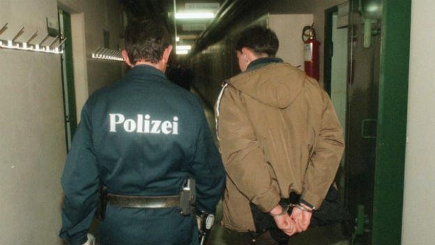 Polizei führt einen Verdächten ab.