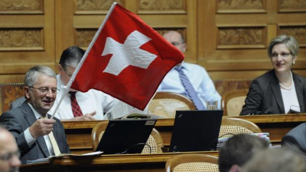 Walter Mueller (FDP/SG), schwenkt eine Schweizerfahne während den Beratungen über das Amtshilfegesuch der USA betreffend der UBS 2010 im Nationalrat.