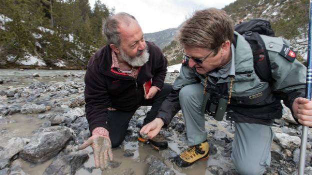 Der Berner Geologe Christian Schluechter und der Nationalpark-Direktor Heinrich Haller (rechts) prüfen die Schlammablagerung im Spoel bei Zernez am 4. April 2013.