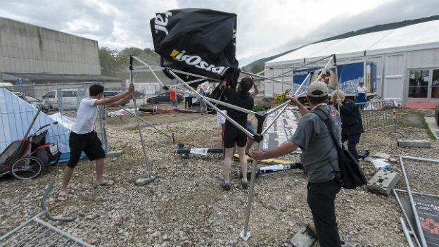 Besucher halten Zeltstangen fest, um sie vor dem Davonwinden zu bewahren.