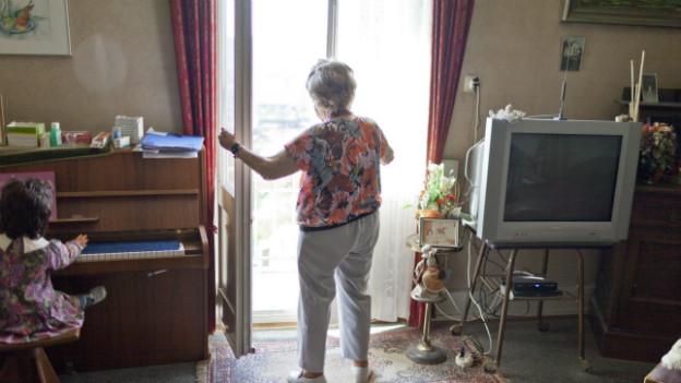 Symbolbild: eine ältere Frau in Biel öffnet das Balkonfenster.