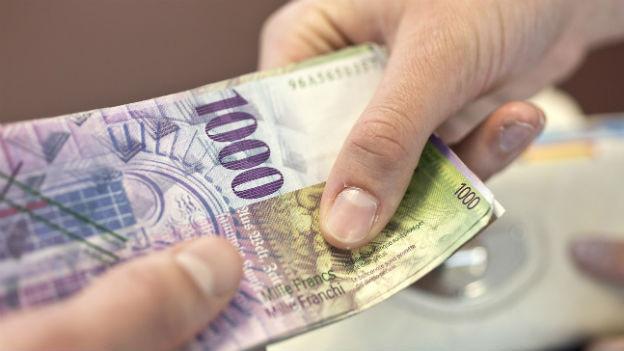 Eine Schweizer Tausendernote wechselt die Hand