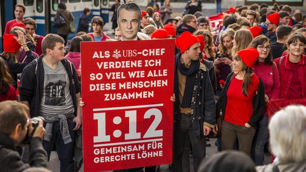 Mitglieder des Initiativ-Komitee 1:12 und der JUSO demonstrieren mit einem Plakat und einem Foto des UBS CEO Sergio Ermotti auf dem Paradeplatz, am 2. November 2013 in Zürich.