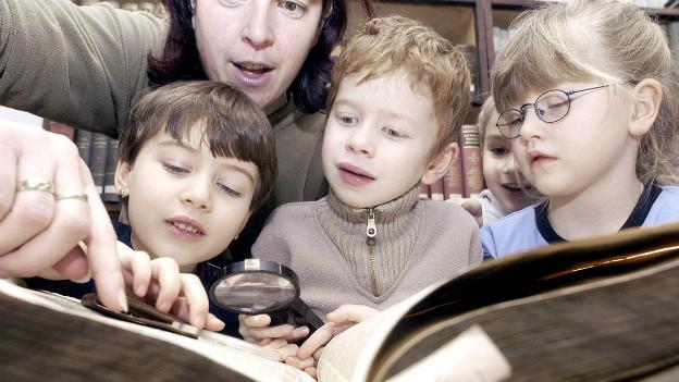 Eine Erzieherin einer deutschen Tagesstätte erklärt Vorschulkindern die Bibel.
