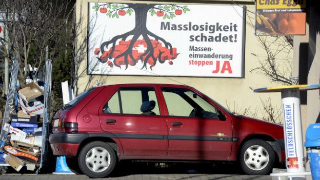 Ein rotes Auto, eingepfercht zwischen Stapeln von Karton und Altpapier, dahinter ein Plakat für die SVP Initiative.
