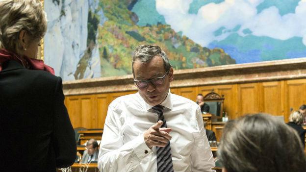 Ruedi Noser diskutiert im Nationalratssaal mit Kollegen