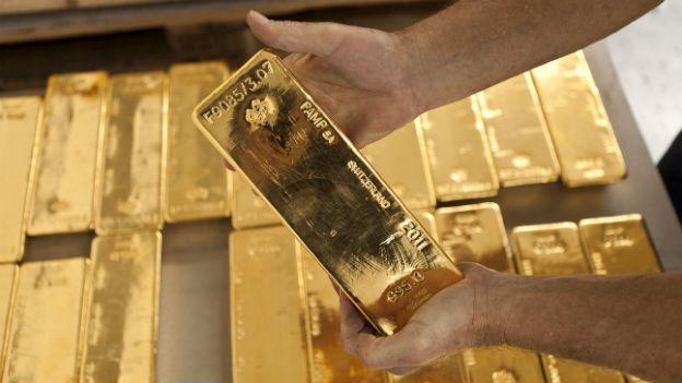 Ein Mitarbeiter hält einen Goldbarren in den Händen