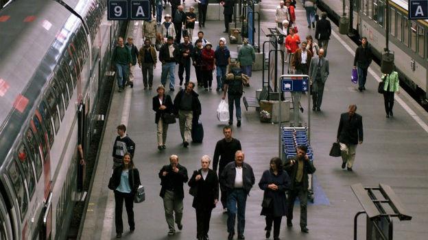 Menschen laufen auf dem Perron zu ihrem Zug