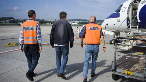 Mann wird von zwei Polizisten zum Flugzeug begleitet.