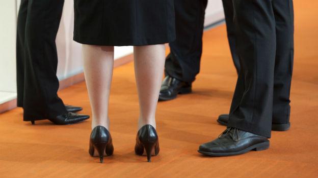 Beine in Managerkleidung von Frauen und Männern.