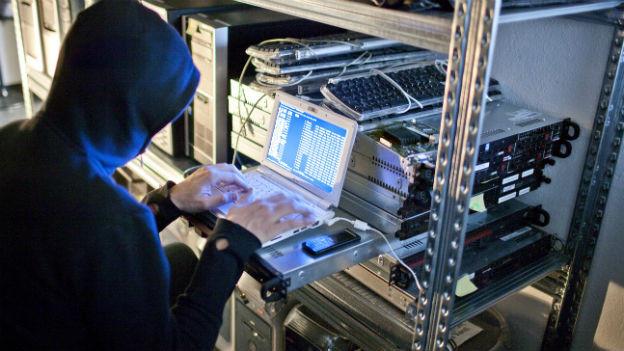 Mann mit Kapuze gibt Befehlszeile am Laptop ein.
