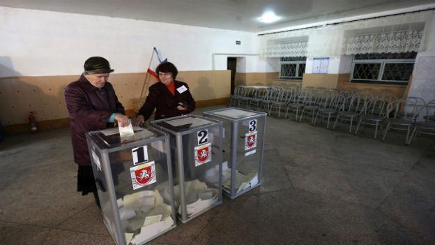 Wahllokal auf der Halbinsel Krim, mit einer Frau, die ihre Stimme vor einer Urne abgibt