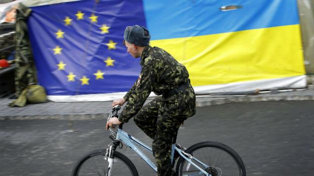 Russischer Soldat fährt auf Velo an EU-Fahne und ukrainische Flage vorbei.