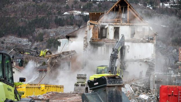 Ein Haus wird abgerissen: Es stehen nur noch die Grundmauern. Davor ist ein gelber Bagger.