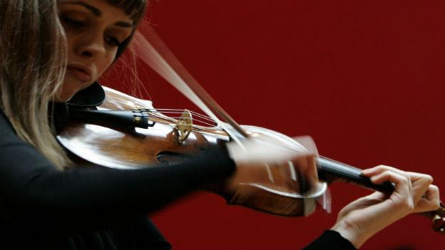 Bild einer Frau, die eine Geige in der Hand hält und spielt