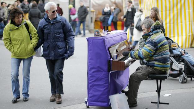 Ein Strassenmusiker in Bern spielt Klavier.
