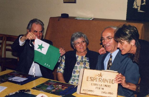 Ein paar Leute sitzen um einen Tisch mit einer Esperanto-Fahne.