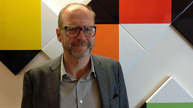 Christoph Doswald vor Max-Bill- Wandrelief im SRF-Radiostudio Zürich