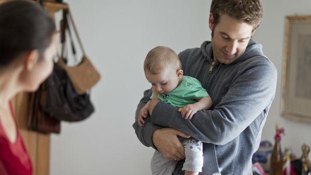 Ein Vater hält ein Kleinkind auf dem Arm, im Vordergrund ist der unscharfe Hinterkopf der Mutter zu sehen.