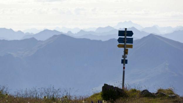 Ein Wegweiser in den Bündner Alpen im Gegenlicht, im Hintergrund ein Alpenpanorama.