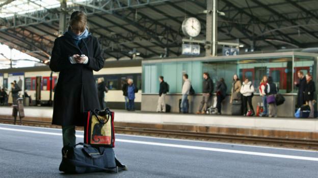 Begehrte User: Eine Pendlerin surft mit ihrem Handy am Bahnhof Lausanne.
