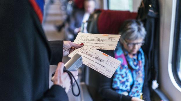 Ein Billetkontrolleur entwertet im Zug zwei Tickets.