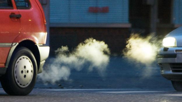 Aus dem Auspuff eines Autos tritt eine Abgaswolke.