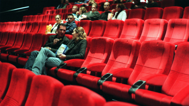 Ein grosser Kinosaal auf dem vereinzelt Leute auf bequemen, roten Stühlen sitzen.