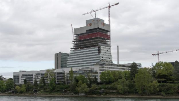 Der eingerüstete Roche-Turm in Basel in der Nähe des Rheins.
