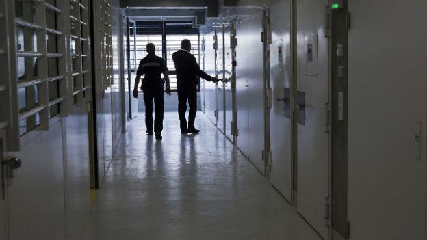 Zwei Wärter gehen durch einen sonst leeren Gang des Genfer Gefängnisses.