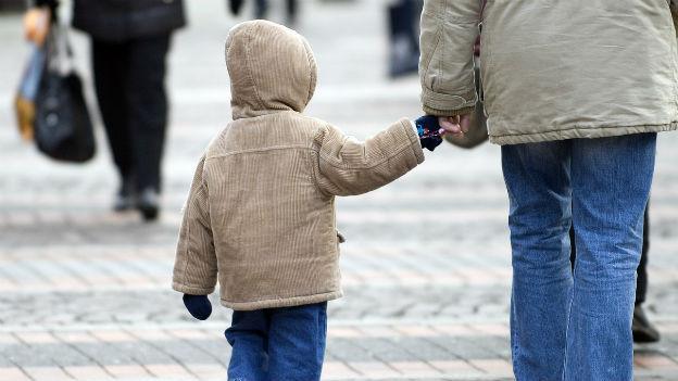 Aufnahme eines Kindes von hinten beim Spazieren. Es gibt seiner Mutter die Hand.