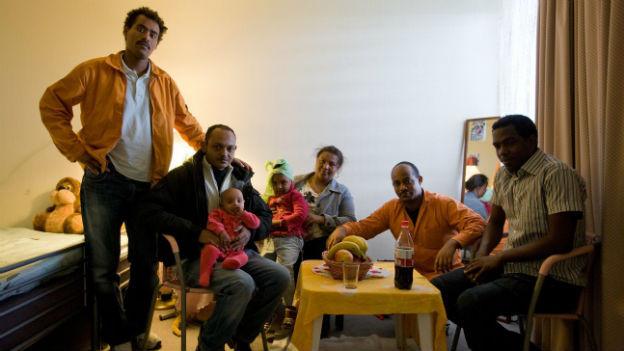 Eine Gruppe Asylsuchender aus Eritrea in einem Zimmer des Übergangszentrums Atlantis.