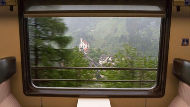 Blick aus dem Fenster eines Abteils in einem alten Zug auf die Kirche von Wassen.