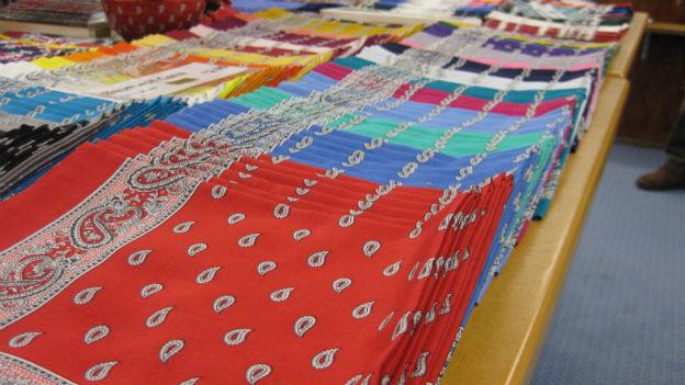 Viele zusammengefaltete Glarner Tüechli liegen auf einem Tisch in einer Fabrik. Im Vordergrund rote, dann folgen andere Farben.