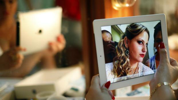 Ein blonde Frau macht mit einem iPad ein Selfie
