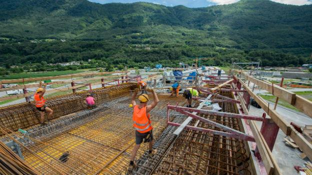 Baustelle am Ceneri-Basistunnel: Im Vordergrund Bauarbeiter, die über Stahlträger balancieren.