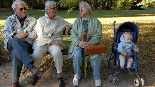 Drei ältere Leute mit Kleinkind sitzen und lachen auf einer Parkbank