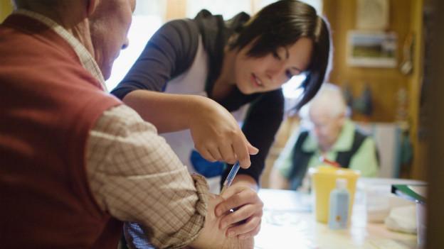 Eine Spitex-Angestellte gibt einem älteren Mann zu Hause eine Spritze.