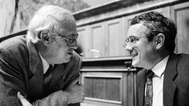 Bundesrat Arnold Koller diskutiert 1989 im Nationalratssaal mit SP-Nationalrat Helmut Hubacher.