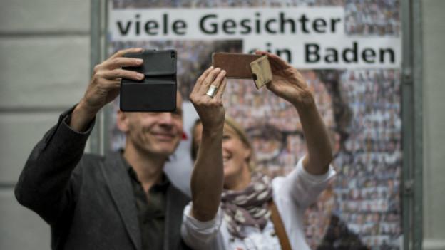 Menschen machen ein Selfie vor einem Portrait von Geri Müller am 25. August in Baden.