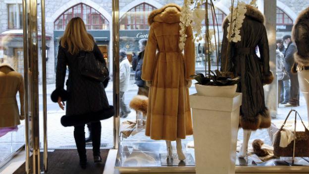 Das Bild zeigt das Schaufenster eines Pelzgeschäfts in St. Moritz von innen. Zwei Pelzmäntel sind ausgestellt. Eine Frau verlässt gerade den Laden.