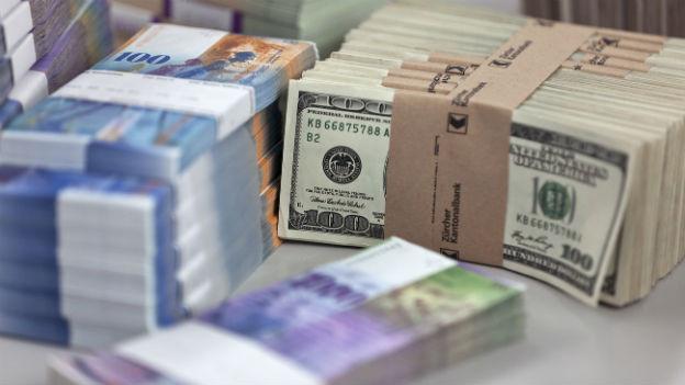 Bündel mit Franken und Dollarnoten auf dem Tisch