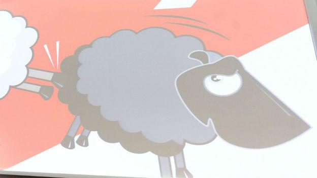 Abstimmungsplakat zur Ausschaffungsinitiative wird an eine Leinwand projiziert. Zu sehen ist das schwarze Schaf, das einen Fusstritt bekommt.