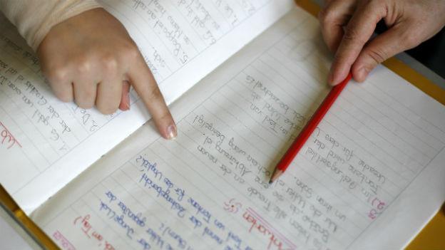 Ein Schulheft und zwei Hände, die jeweils mit einem Finger auf einen handgeschriebenen Text zeigen.