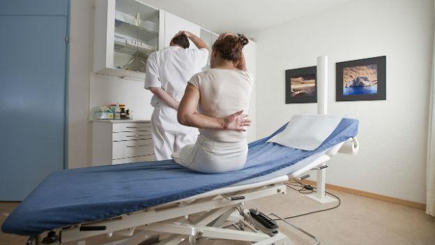 Untersuchungszimmer in einer Arztpraxis: Eine Patientin sitzt mit dem Rücken zum Betrachter auf einer Liege.