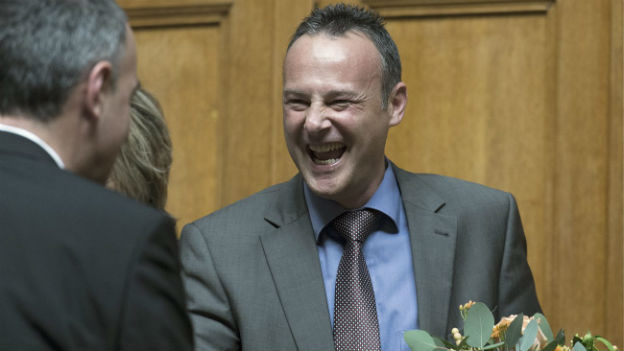 Das Bild zeigt, wie jemand Stéphane Rossini gratuliert. Rossini strahlt übers ganze Gesicht.