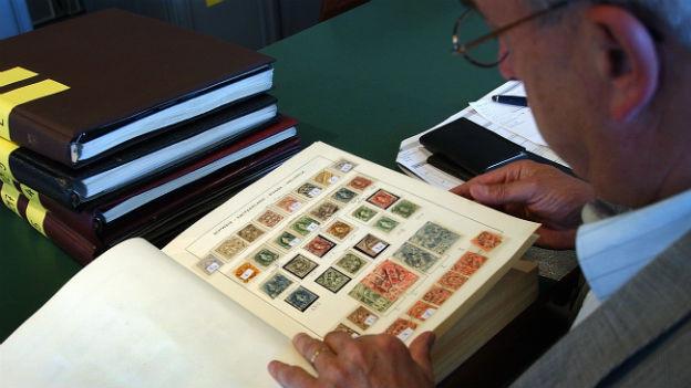 Ein Briefmarkensammler begutachtet im Vorfeld der Auktion einen der vielen Tausend Alben auf Qualität und Zustand der Marken.