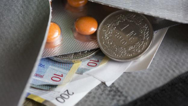 Das Bild zeigt ein geöffnetes Portemonnaie im Grossformat. Sichtbar sind Tabletten, Münzen und Noten.